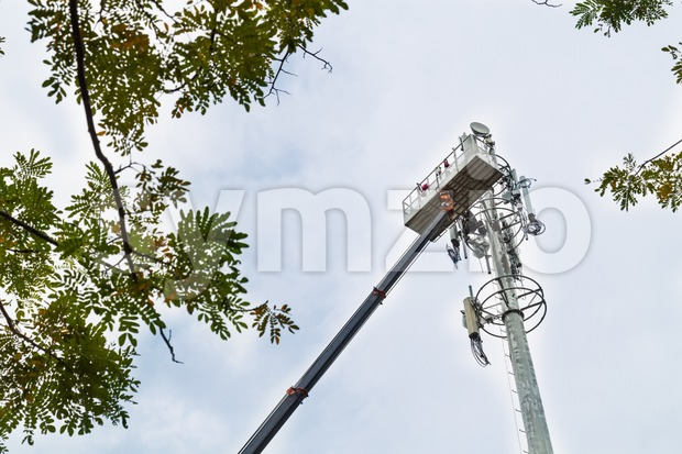 Two workers on crane installing mobile network communication antenna Stock Photo