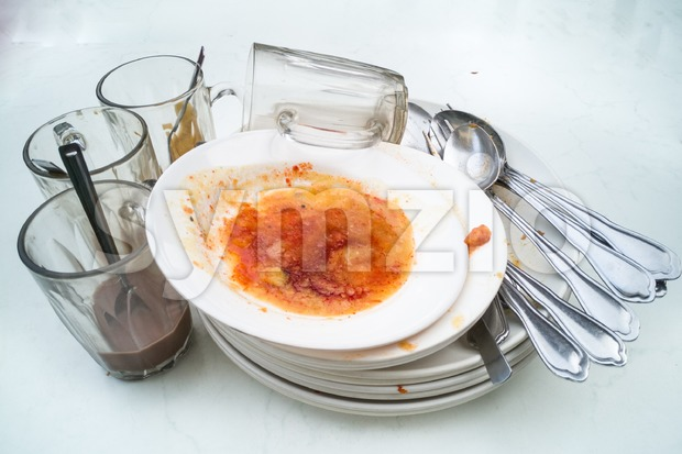 Pile of dirty oily plates, glass, fork spoons after meal Stock Photo