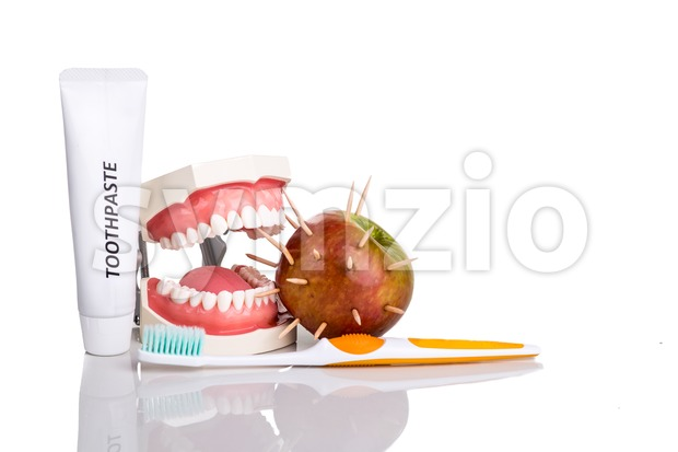 Conceptual of model mouth bite  apple with thorns, toothbrush, toothpaste,  denote sharp pain when bite
