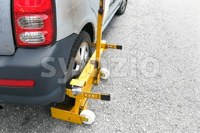 Car wheel clamp on street for illegal parking Stock Photo