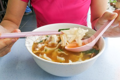 Person eating flat flour noodle soup or Pan Mee cuisine Stock Photo