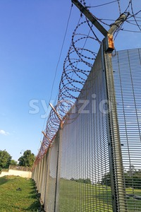 Sharp barbed wire on security fence protecti secure private space Stock Photo
