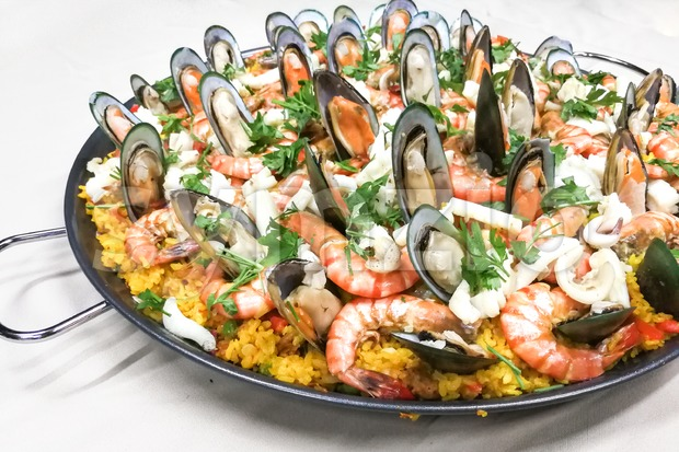 Close-up on delicious spanish paella rice with prawn, mussels, squids in pan served on table