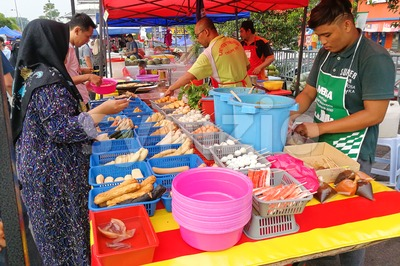 KUALA LUMPUR, MALAYSIA, May 29, 2016: Muslim shopper buying food from street vendor for breaking fast or iftar Stock Photo
