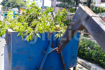 Close-up garbage container latch with truck full of garden refuse Stock Photo