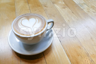 Cappuccino foam art with love heart shape on table Stock Photo
