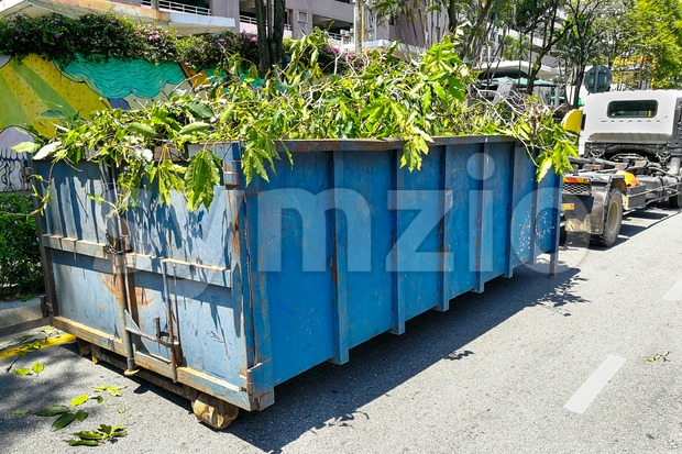 Garbage container latch with truck full of garden refuse woods Stock Photo