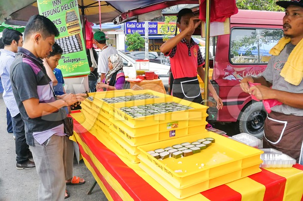 KUALA LUMPUR, MALAYSIA, June 2, 2017: Muslim shopper buying sweet desserts from street stall vendor for breaking fast or iftar Stock Photo