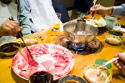 People dining with raw Japanese kobe beef shabu-shabu steamboat Stock Photo