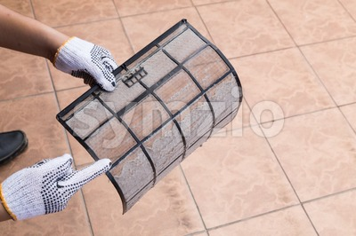 Person pointing on thick dirty dust on air conditioner filter Stock Photo