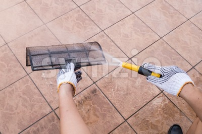 Person spraying water onto air conditioner filter to clean dust Stock Photo