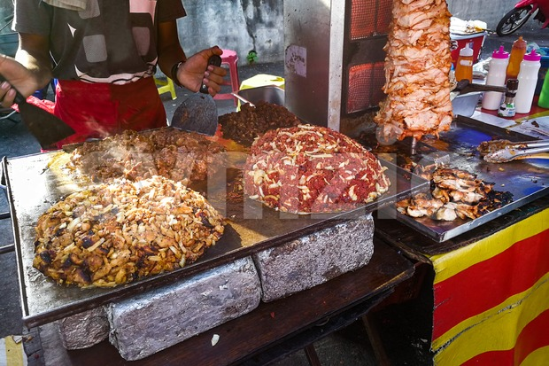 Person grilling and roasting meat for shawarma pita bread meal at street stall for muslim iftar or breaking fast in ...