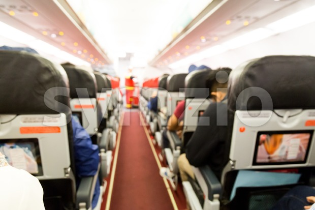 Defocused airplane cabin interior with seats, passengers and red flooring