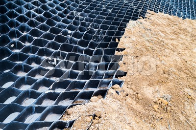 Close up on slope erosion control grids on steep slope. Stock Photo