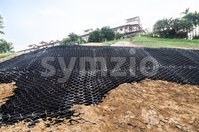 Slope erosion control with grids and earth on steep slope. Stock Photo