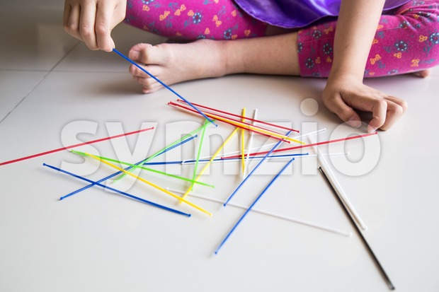 Series of kid playing pick up sticks fun game Stock Photo