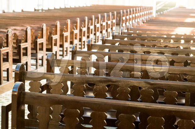 Rows of empty pew benches inside chapel church Stock Photo