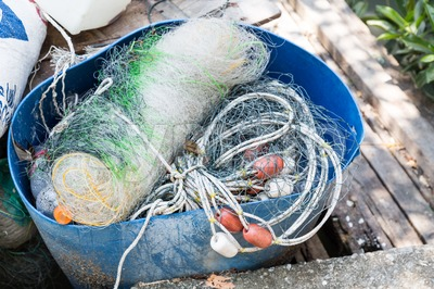 Traditional fisherman net, float and rope folded up Stock Photo