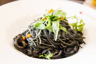 Close-up on simple squid ink pasta with squid and vegetable Stock Photo