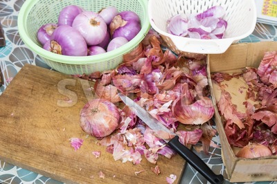 Onion skin being prepared peeled with knife, chopping board colander Stock Photo