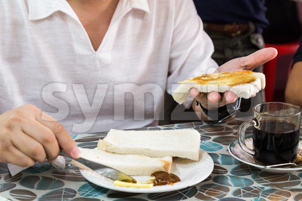 Series of person applying butter and kaya to steamed bread Stock Photo