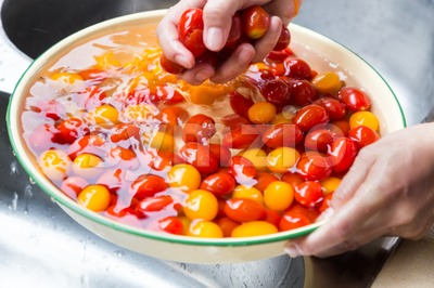 Hand washing cherry tomato with running water in household sink Stock Photo