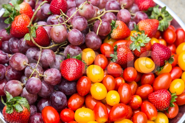 Close-up on fresh and sweet organic grapes, strawberries, cherry tomatoes Stock Photo