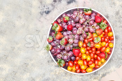 Tray of fresh and sweet organic grapes, strawberries, cherry tomatoes Stock Photo