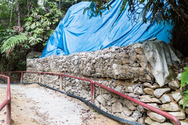 Slope and earth retention wall management with rocks and wire mesh cage system in tropical hilly terrain