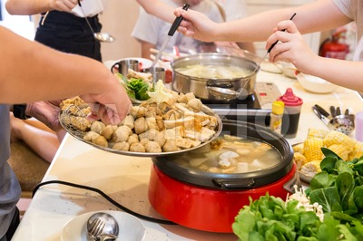 Hand adding ingredient into Asian steamboat pot meal Stock Photo
