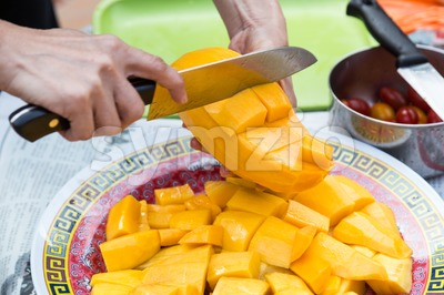 Hand holding knife cutting sweet delicious organic mango Stock Photo