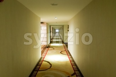 Long dark corridor with light from ceiling Stock Photo