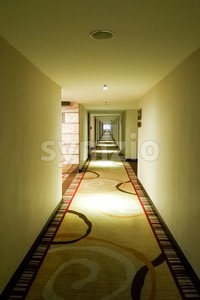 Long dark corridor with light from ceiling in vertical format Stock Photo