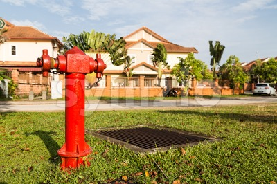 Red fire hydrant at strategic residential ready for emergency Stock Photo