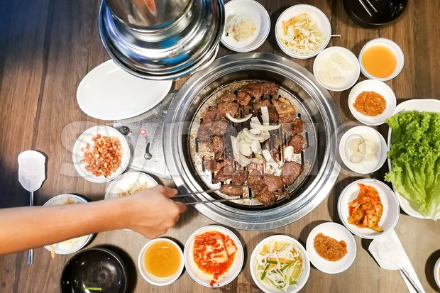 Person barbecue beef on bbq pit during korean meal set Stock Photo