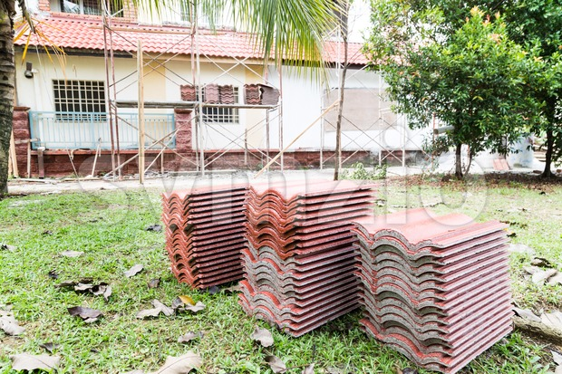 Stack of roof tiles with house on construction in background Stock Photo