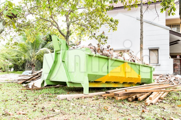 Construction rubbish bin with loads at construction site. Stock Photo