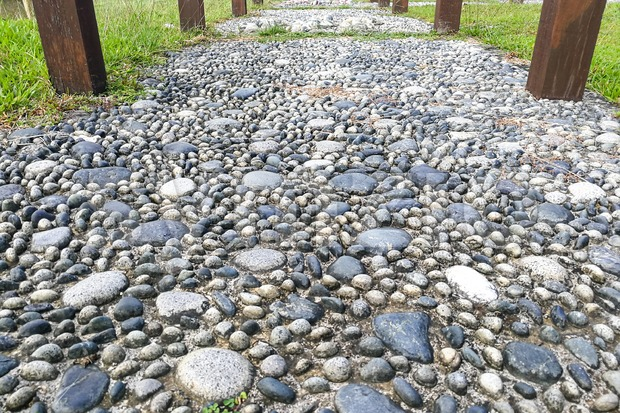 Close-up on pressure points pebble stones at foot reflexology park Stock Photo