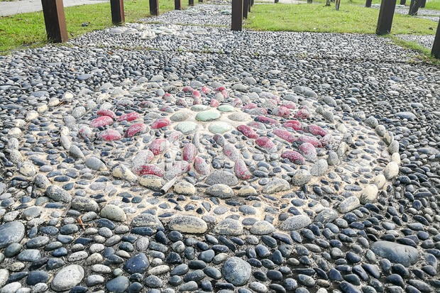 Close-up on pebble stones at foot reflexology park. Walking on them stimulates pressure points, promotes health and well-being.