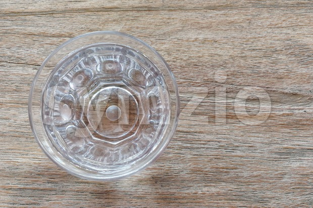 Glass of pure purified mineral drinking water on wooden table