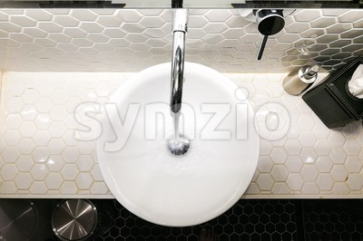 Modern contemporary wash basin with running water from tap faucet Stock Photo
