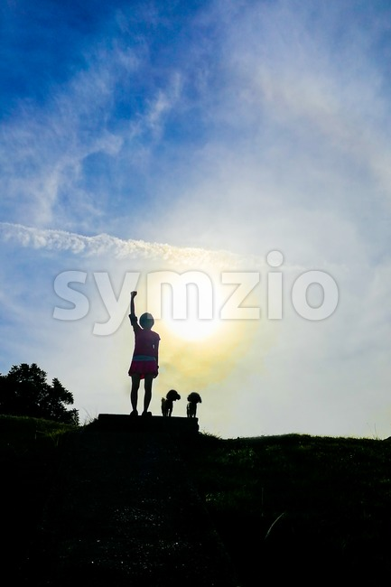 Silhouette woman hiker with dogs raises hands on hill peak Stock Photo