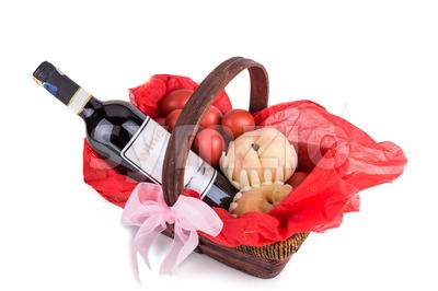 Hamper basket consist red eggs, peach and red wine Stock Photo