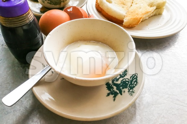 Asian traditional breakfast combination of half boiled eggs, toast bread with butter and kaya and coffee