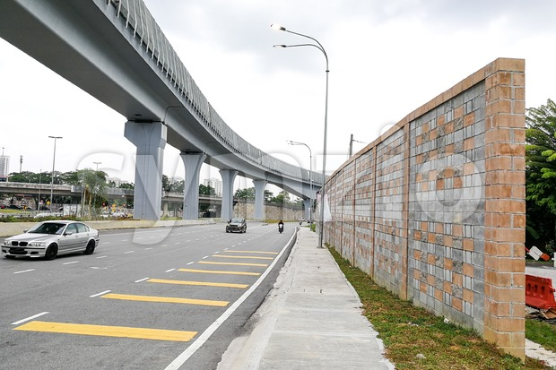 Concrete sound barrier wall next to busy highway and elevated rail track, isolate noise.