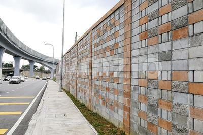 Concrete sound barrier wall next to busy highway rail track Stock Photo