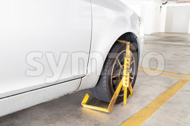 Front car wheel clamped for illegal parking, a violation at commercial car parks