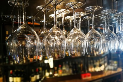 Empty wine glasses hanging on rack in bar Stock Photo