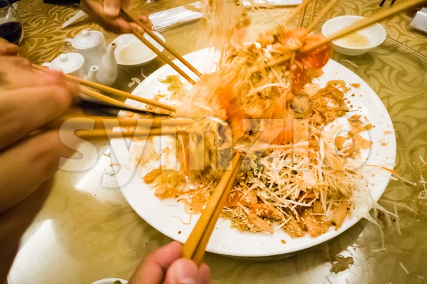 Motion hands with chopsticks tossing  Yee Sang meal in Malaysia Stock Photo