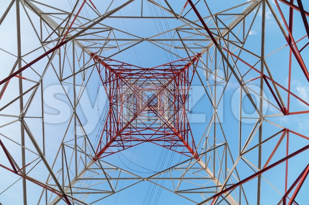 Perspective view under a huge red electricity supply pylon against blue sky